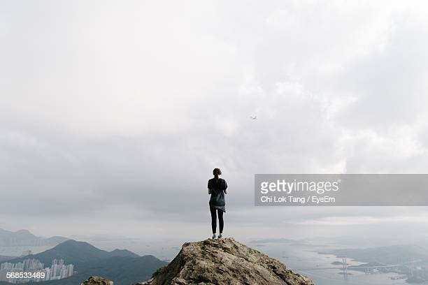 Woman Standing On Top Of Mountain Against Cloudy Sky