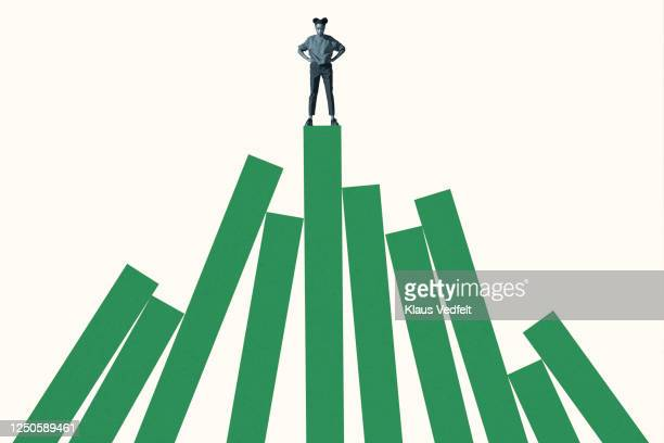 woman standing on top of tall green bar graph - 柔軟性 ストックフォトと画像