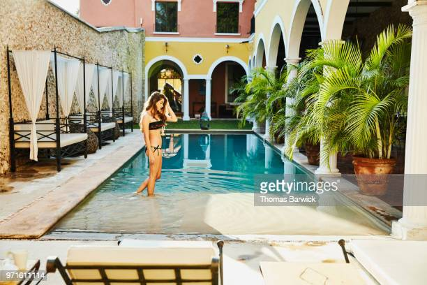 Woman standing on top step of pool in courtyard of boutique hotel