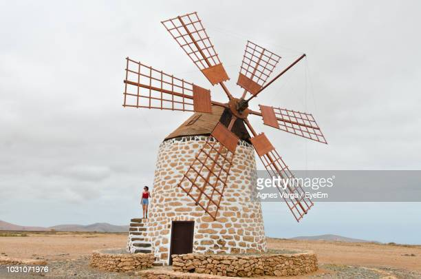 woman standing on traditional windmill against sky - old windmill stock photos and pictures