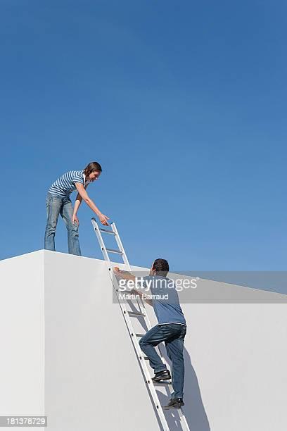 Frau stehend an der Wand und Mann mit Leiter im Freien