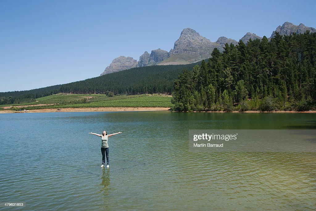 Woman standing on water with arms up : Stock Photo