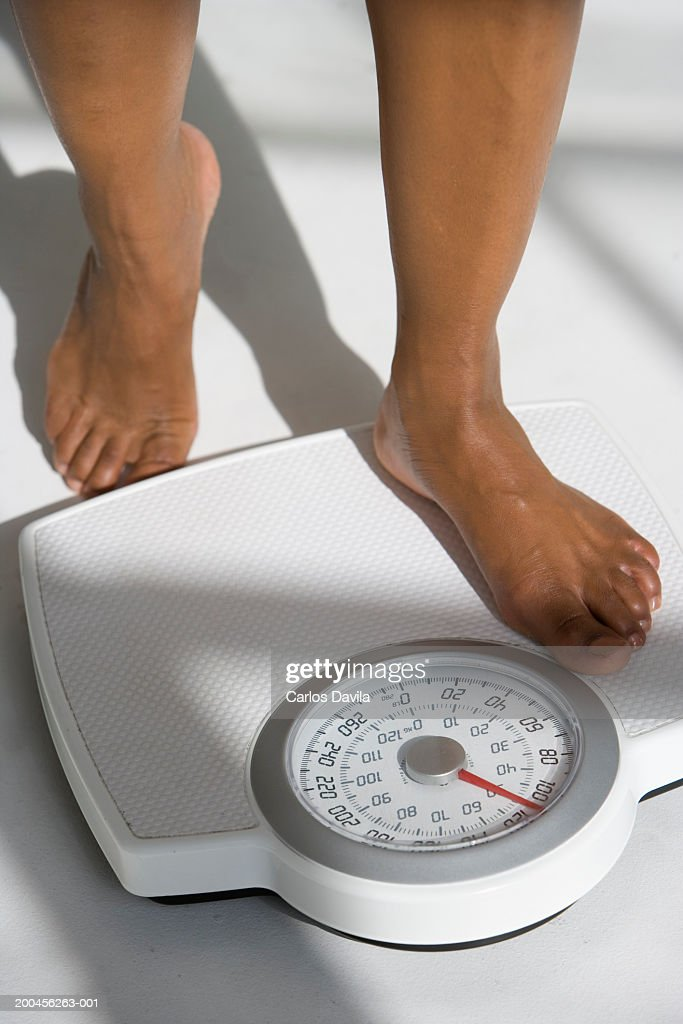 Closeup Of A Woman Standing On A Weighing Scales High-Res