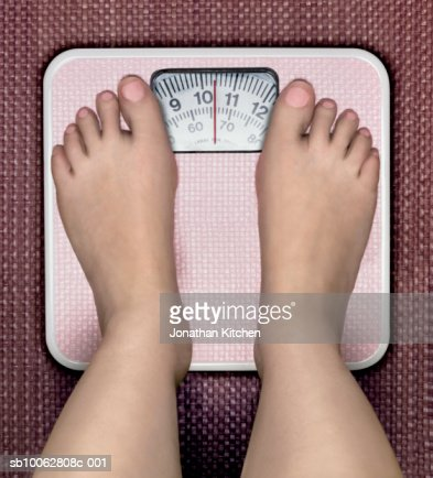 Young Woman Standing On Classic Analogue Weight Scale