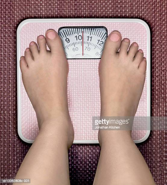 Woman standing on weighing scales, low section