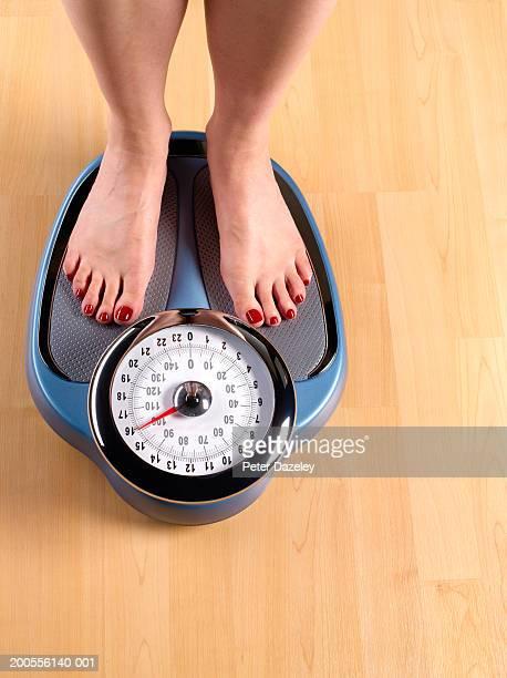 woman standing on weighing scales on wooden floor, low section - körperbewusstsein stock-fotos und bilder