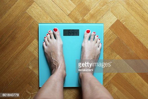 Woman Standing On Weighing Scales Stock Photo - Getty Images