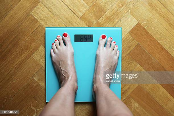 woman standing on weighing scales - weight scale stock pictures, royalty-free photos & images