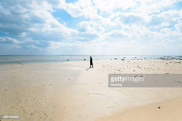 Woman standing on winter beach in strong sunshine