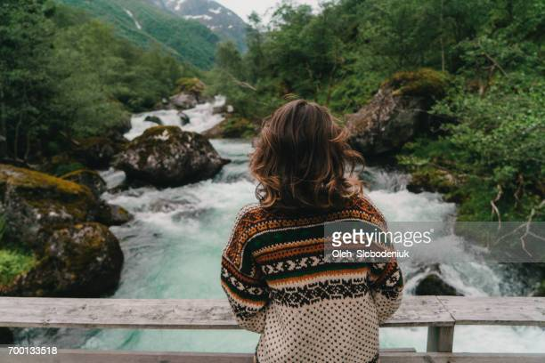 woman standing on wooden bridge on the mountain river in norway - knitted stock pictures, royalty-free photos & images