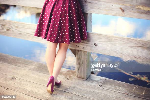 Woman standing on wooden dock over still lake