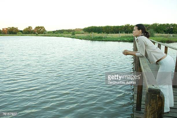 woman standing on wooden footbridge over lake, looking into distance - beautiful women bent over stock photos and pictures