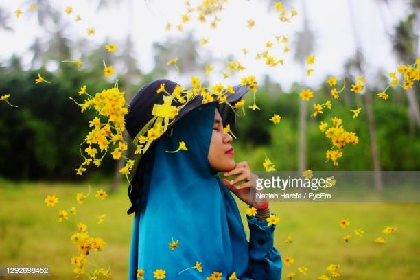 woman standing on yellow flowering plants on field - solo adulti foto e immagini stock