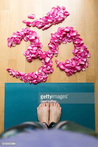 Woman standing on yoga mat in front of petals