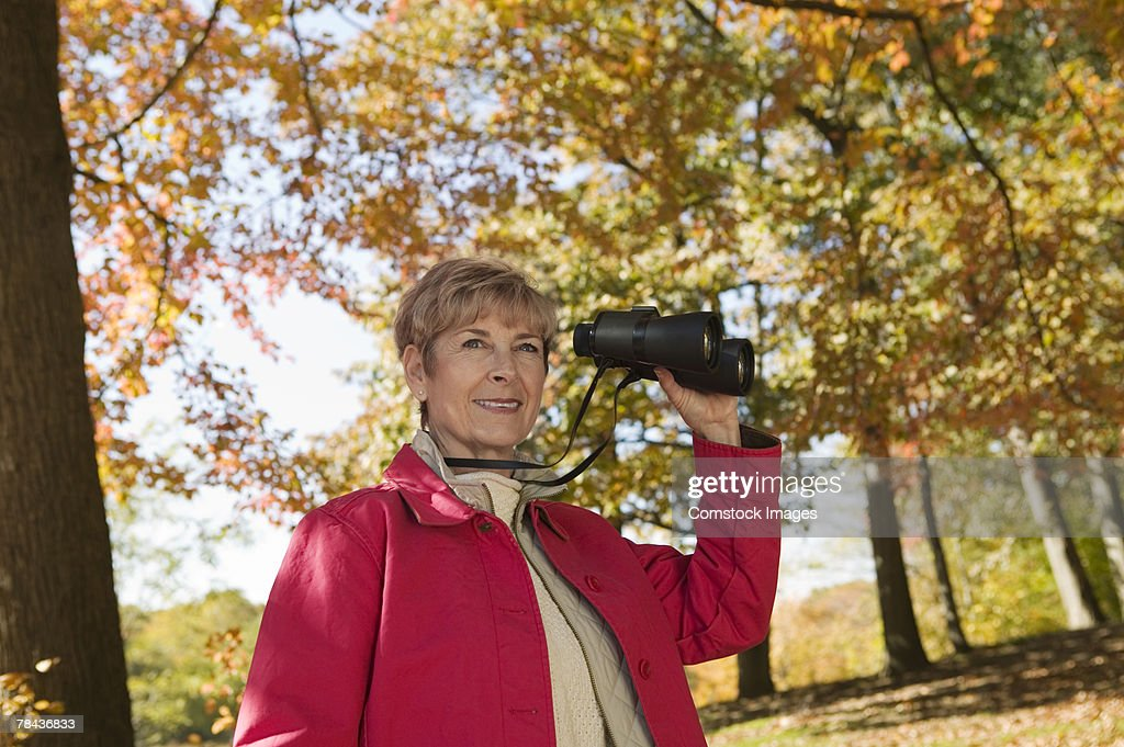 Woman standing outdoor with binoculars : Stockfoto