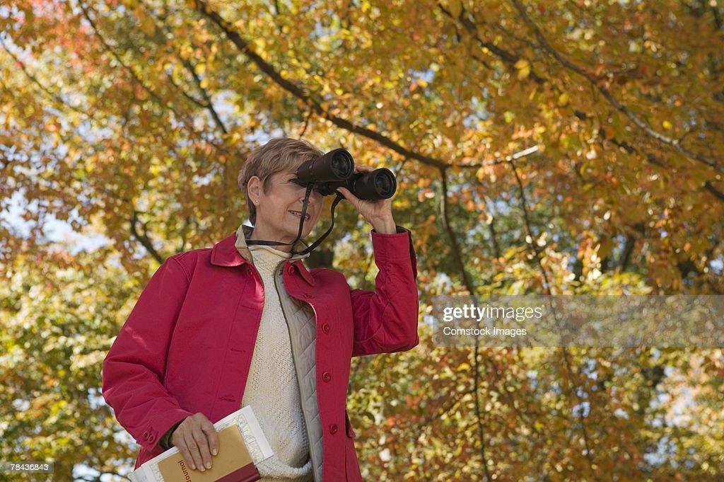 Woman standing outdoor with binoculars : Stockfoto