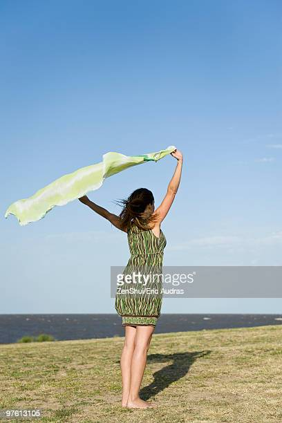 woman standing outdoors, holding up shawl in wind, full length - ストール ストックフォトと画像