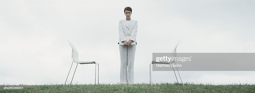 Woman standing outdoors on grass between two chairs in front of overcast sky : Stockfoto