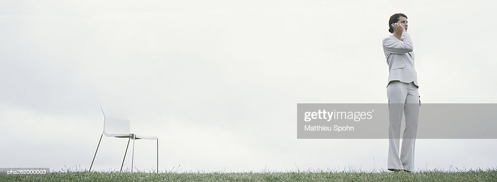Woman standing outdoors on grass talking on cell phone, with chair, in front of overcast sky : Stockfoto