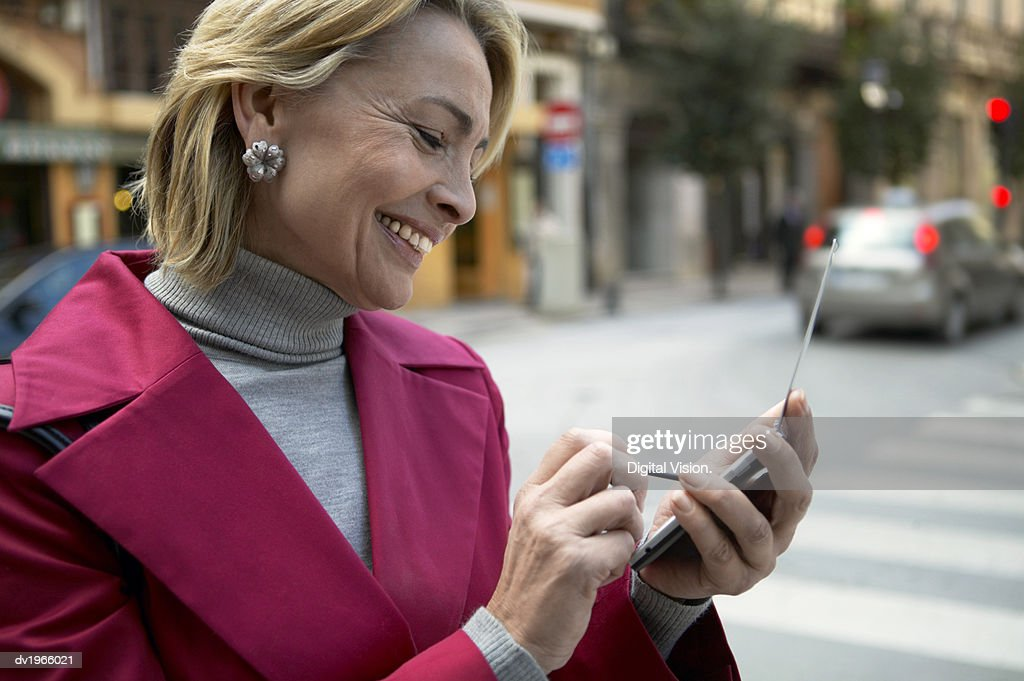 Woman Standing Outdoors Using a Mobile Phone and a Stylus : Stock Photo
