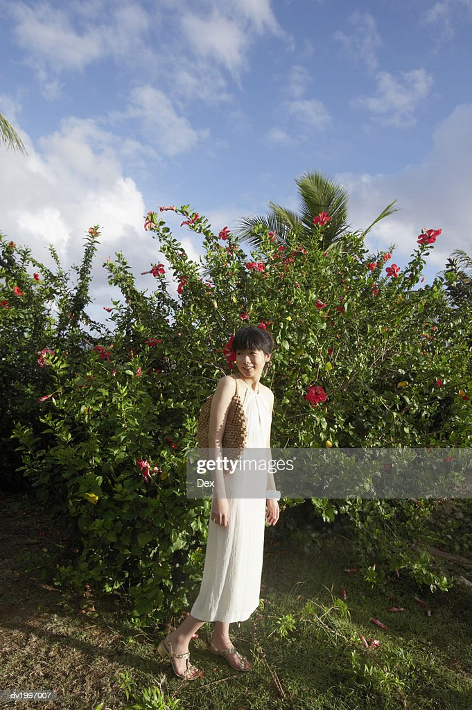 Woman Standing Outdoors Wearing a Dress and a Flower in Her Hair : Stock Photo