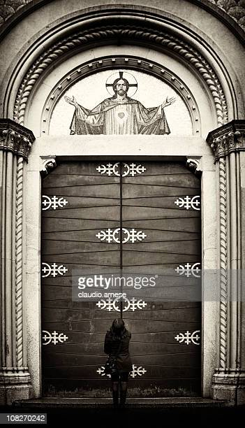 woman standing outside church door - catholic baptism stock pictures, royalty-free photos & images