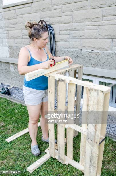 Woman standing outside to make a wooden sofa during day of summer