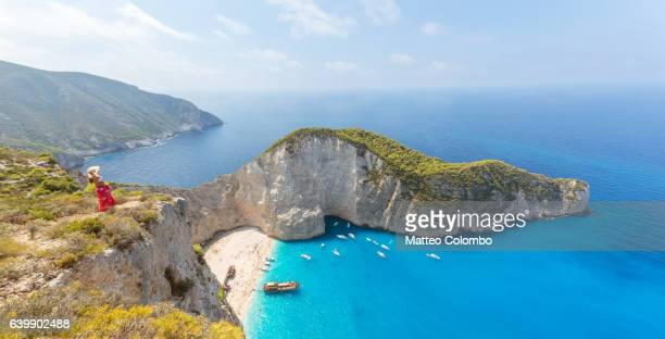 woman standing over famous navagio beach. zakynthos, greek islands, greece - islas griegas fotografías e imágenes de stock