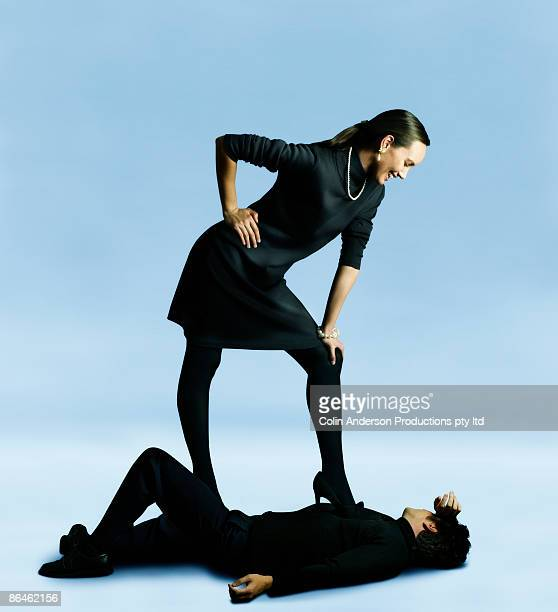 Woman standing over man lying down