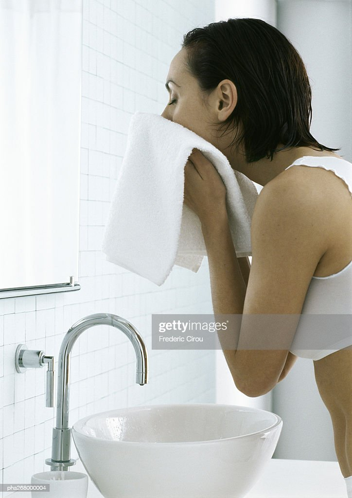 Woman standing over sink drying face with towel : Stockfoto