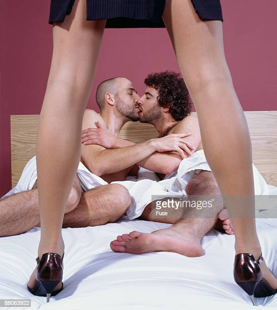 Woman Standing Over Two Men Kissing in Bed