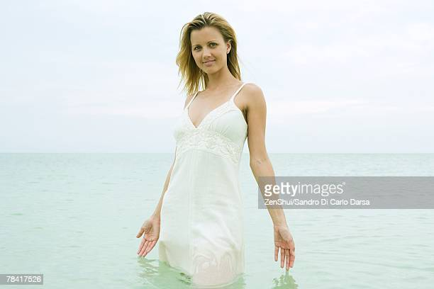 woman standing thigh deep in ocean, touching surface of water, smiling at camera - waist deep in water stock pictures, royalty-free photos & images