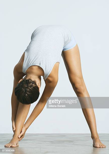 Woman standing, touching ankle