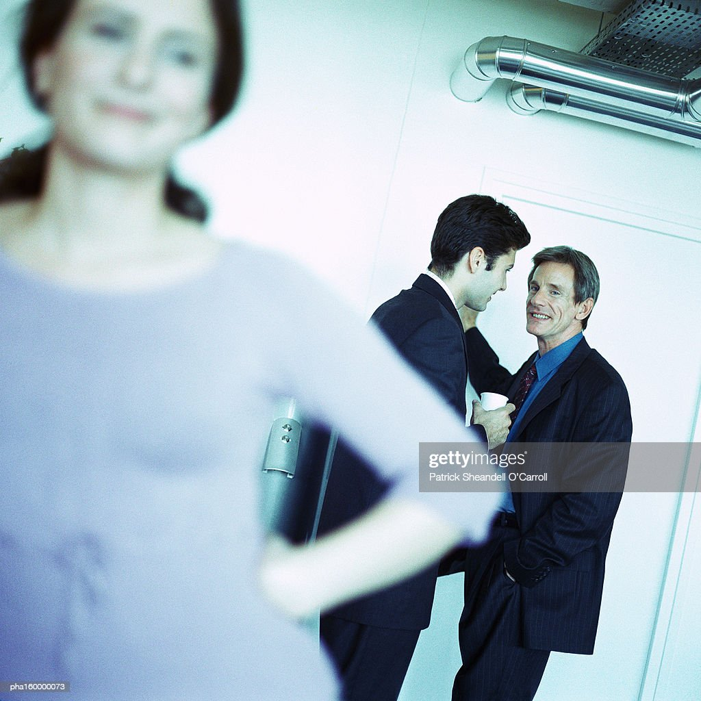 Woman standing, two men in background, focus on background. : Stockfoto