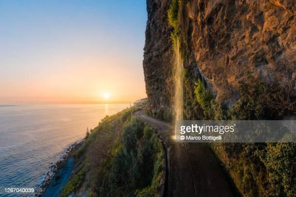 woman standing under a waterfall on a coastal road at sunset, madeira island, portugal - madeira fotografías e imágenes de stock