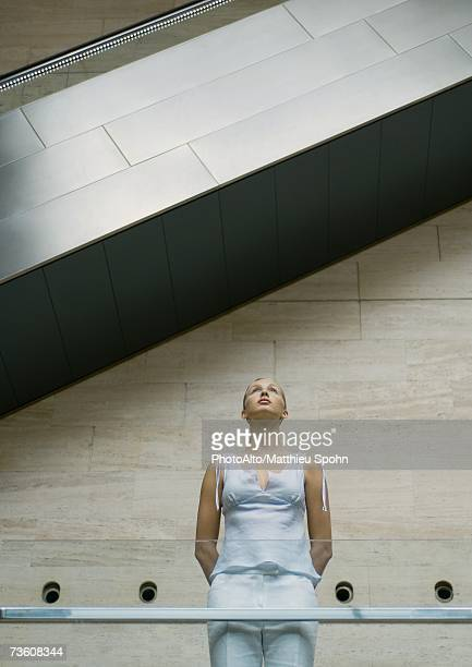 Woman standing under escalator, low angle view