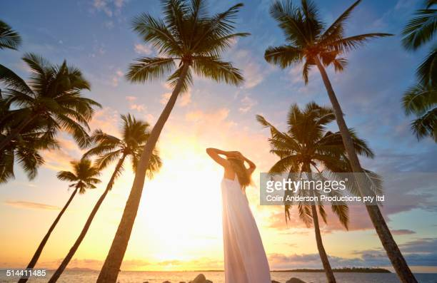 Woman standing under palm trees