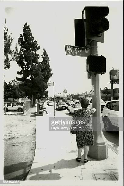 woman standing under stop light - hollywood california stock photos and pictures