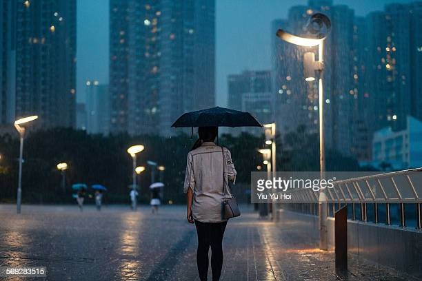 Woman standing under the heavy rain in city street