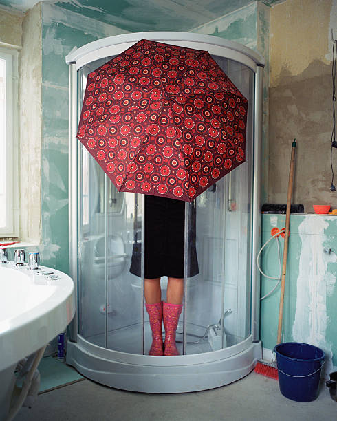 Woman standing under umbrella in shower stall