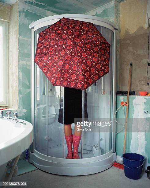 woman standing under umbrella in shower stall - irony stock pictures, royalty-free photos & images