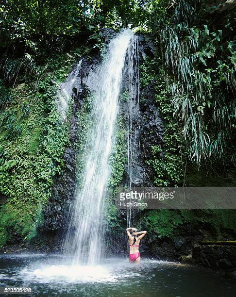 woman standing under waterfall - hugh sitton stock-fotos und bilder