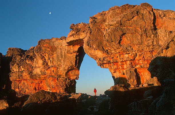 Woman standing underneath rock arch, Wolfberg Arch, Cederberg, Western Cape Province, South Africa