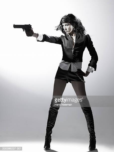 Woman standing up, pointing gun,  side view
