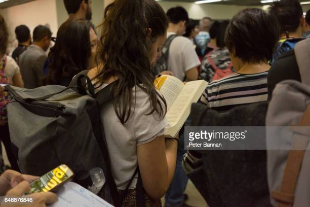 Woman standing waiting in airport arrival queue reads book