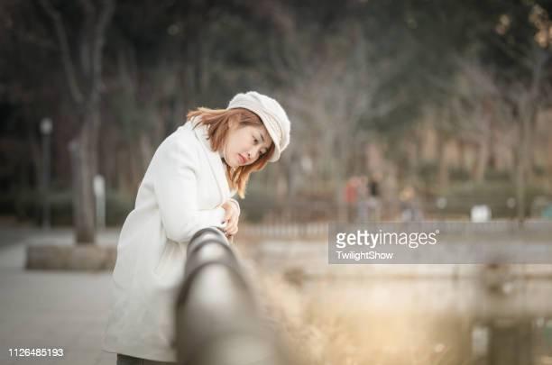 一人で公園で自然観女性立って見てサンセット - 防寒着 ストックフォトと画像
