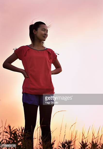 a woman standing wearing jogging wear at sunset - moody sky stock pictures, royalty-free photos & images