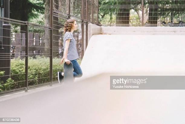 a woman standing with a skateboard - yusuke nishizawa stock-fotos und bilder
