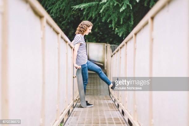 a woman standing with a skateboard - yusuke nishizawa ストックフォトと画像