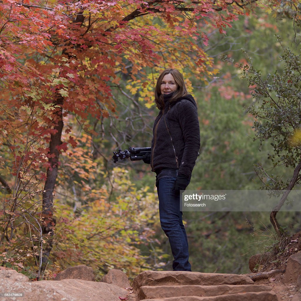 Woman standing with a tripod in a forest : Stock Photo